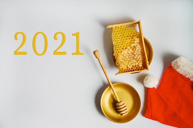 2021年の新年、蜂蜜製品。健康的な自然食品の概念。養蜂のためのクリスマスと新年の背景