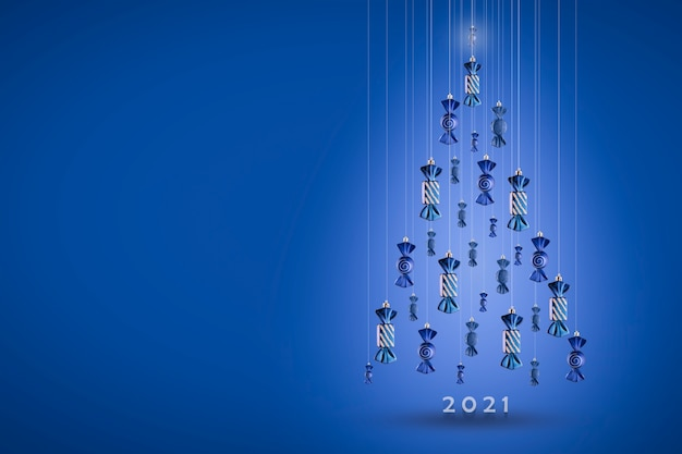 New year 2021-an inscription under the christmas tree made of candy christmas toys suspended on a string. blue pleasant wall, copy space christmas card.