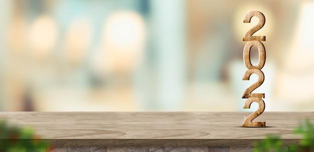 新年2022年(3dレンダリング)ぼかし葉の前景とぼかし抽象的なボケ光の家の背景、製品の表示のためのモックアップバナー、休日のお祝いグリーティングカードで茶色の木製テーブルに