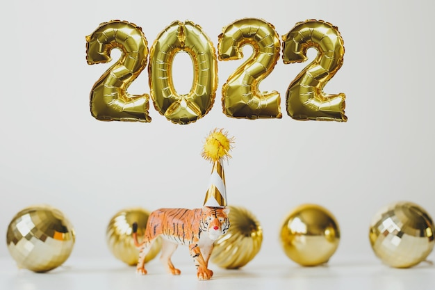 New year 2022 foil gold balloons number 2022 and tiger symbol of the chinese new year in party cap
