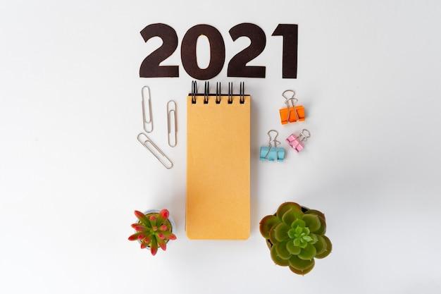 Новогодние числа 2022 года и канцелярские товары на белом столе