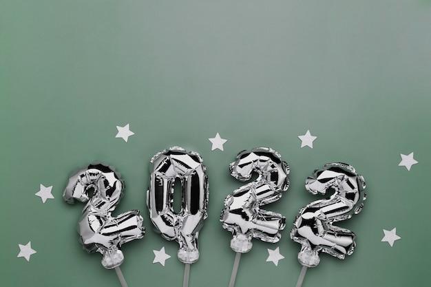 Новый год 2022 или рождество зеленый фон плоская планировка. вид сверху на серебряный воздушный шар 2022 года или металлические цифры на палочках со звездами. концепция приглашения или поздравительной открытки. праздничное настроение. фото высокого качества