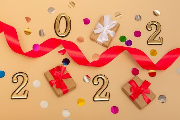 2022年の新年。ベージュの背景に新年のモックアップを表示:赤いリボン、ギフトボックス、ゴールドの数字、色とりどりの輝き。はがき、招待状のレイアウト。