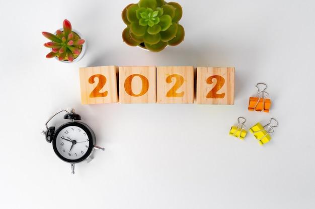 Новый год 2022 деревянные кубики на рабочем столе с канцелярскими принадлежностями