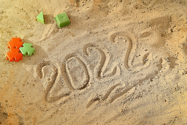 New year 2022 written by hand on wet sand on a beach by sea countdown on the eve of the holiday