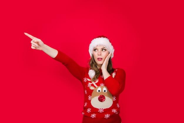 新年の広告。離れて指しているクリスマスの女性。広告。販売と割引。シーズンセール。クリスマスの帽子をかぶった女性が指さします。スペースをコピーします。