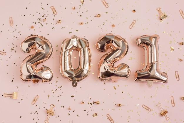 新年とクリスマス2021年のお祝いのコンセプト。 2021年の数字と紙吹雪の形のホイル風船