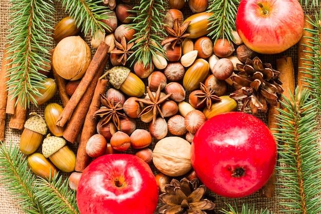 견과류, 사과, 아니스, 계피 스틱 등 유기농 천연 재료의 새해와 크리스마스 배경. 새해 휴일의 개념입니다.