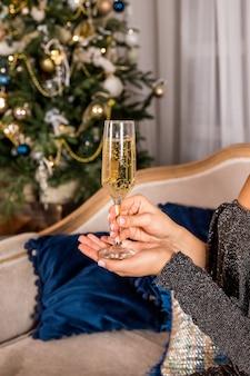 Новый год и рождество с шампанским перед елкой. женская рука