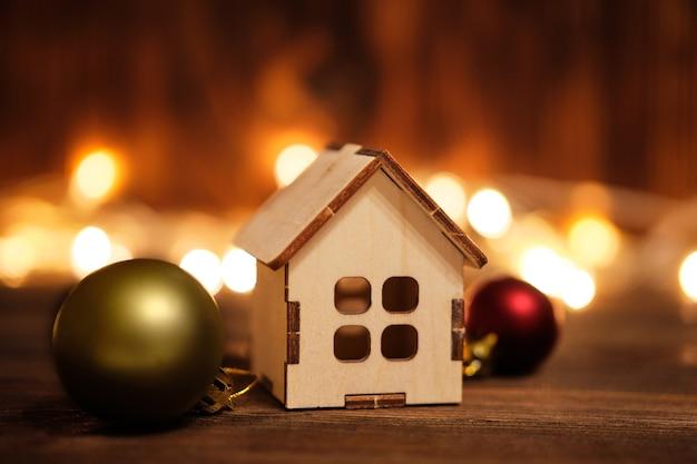 花輪とおもちゃの家と木製の背景に新年とクリスマスのコンセプト