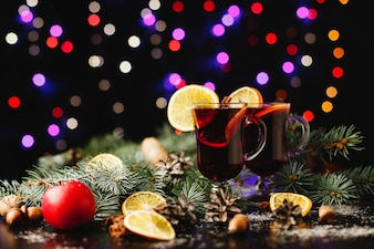 New Year and Christmas decor. Glasses with mulled wine stand on table with oranges