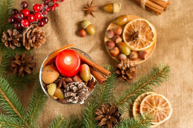 黄麻布を背景に赤いろうそくと構成のベリー、コーン、ナッツ、オレンジスライスの新年とクリスマスの装飾。