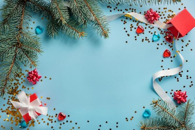 전나무 가지, 크리스마스 공, 색종이 및 복사 공간 파란색 배경에 선물로 만든 새 해와 크리스마스 프레임. 크리스마스와 새 해 액세서리와 함께 평면 위치 구성.