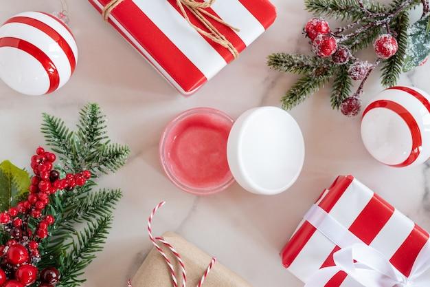여성을 위한 새해 및 크리스마스 선물, 휴가 쇼핑, 개인 관리 및 미용, 얼굴 크림 또는 스크럽, 녹색 전나무 나뭇가지, 붉은 열매, 대리석 배경의 선물 상자.
