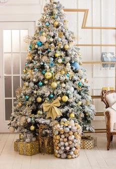 大きく美しい装飾されたクリスマスツリーの下で新年とクリスマスプレゼント