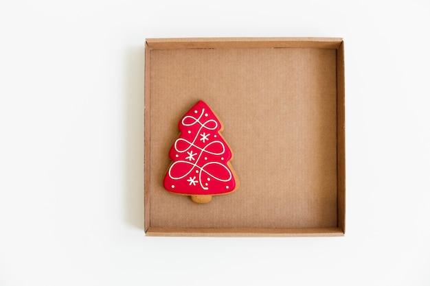 クラフトブラウンボックスの新年とクリスマスのジンジャーブレッドクッキー。木の形。上面図。白色の背景。ミニマリストスタイル。