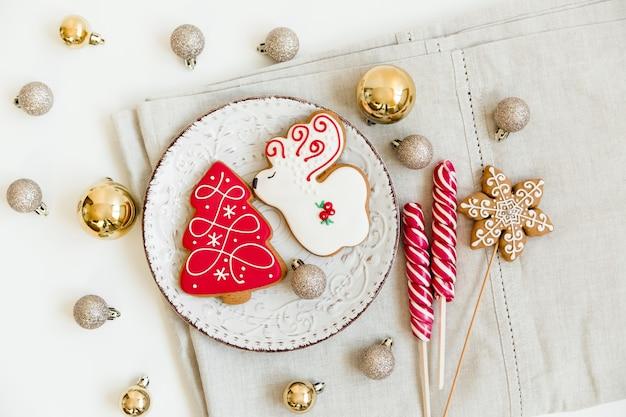 새 해와 크리스마스 진저 쿠키와 크리스마스 공 및 사탕. 사슴과 나무 모양. 크리스마스 flatlay. 접시와 식탁보에