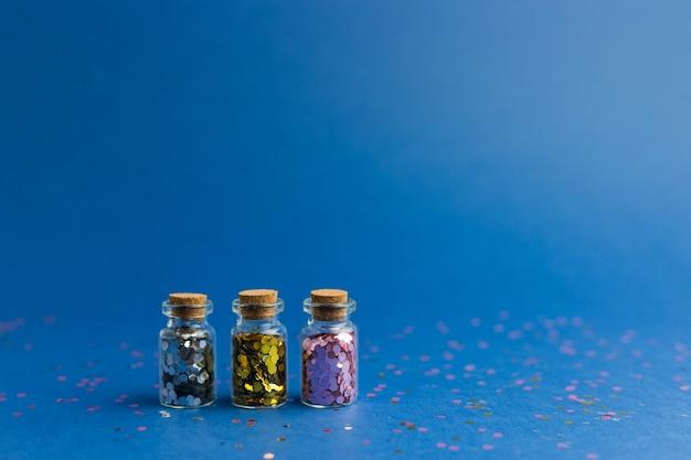 Новый год и рождество праздник синий фон. праздники, покупки и концепция продаж. три маленькие стеклянные бутылки с конфетти.