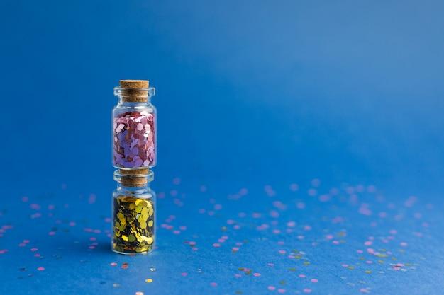 Новый год и рождество праздник синий фон. праздники, покупки и концепция продаж. две маленькие стеклянные бутылки с конфетти.