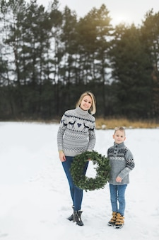 Новогодние и рождественские праздники. кавказская мама с сыном держат украшенный рождественский венок