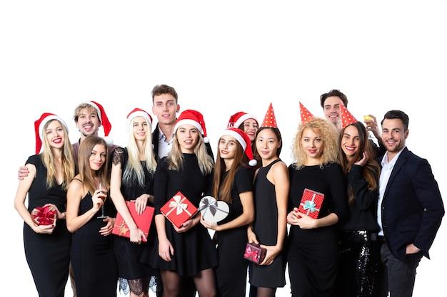 元日とクリスマス、楽しい人々が休日を祝います。楽しんでいる白い背景の上の黒い古典的な服を着た友人のグループ。
