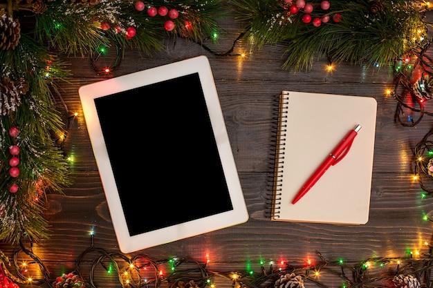 새해와 크리스마스 목컵. 태블릿, 나무 배경에 크리스마스 조명이 있는 스마트폰, 텍스트를 위한 공간, 카피스페이스. 위에서. 휴일 겨울 계획 개념입니다. 플랫 레이 스타일.