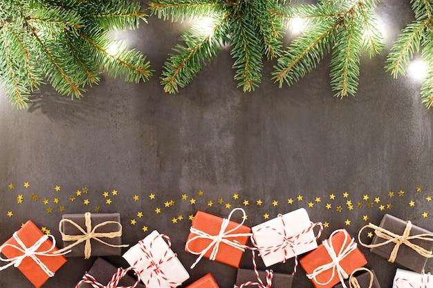 新年とクリスマスの表面に黒、白、赤のラップされたギフトボックス、色付きロープ、スプルース/モミの枝、明るい花輪、黒い表面に小さな金の星。フラットレイアウト、コピースペース