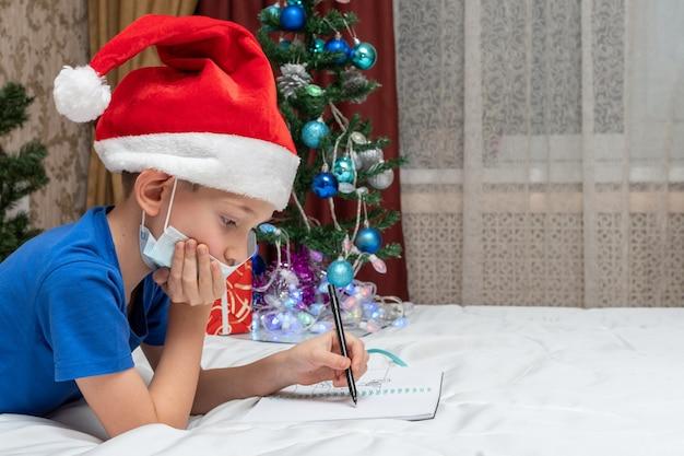 코로나 바이러스 봉쇄 중 새해 및 크리스마스 전통. 의료 마스크와 빨간 모자에 작은 백인 소년 집에서 산타에게 편지를 쓰고 있습니다. 격리 크리스마스 개념.
