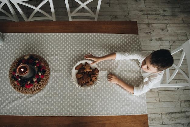 自宅で新年。白いセーターを着た男の子。休日を見越して。ジンジャーブレッドとキッチンでお茶を飲みます。クリスマスツリーの灰色のテーブルクロス。白い椅子、木製のテーブル。