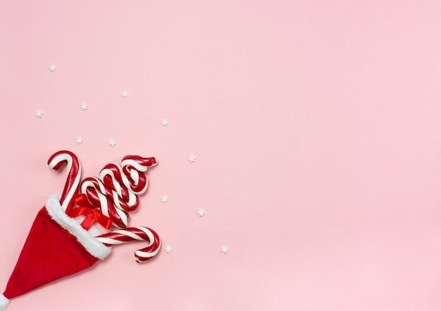 새 해 배경. 크리스마스 트리 롤리팝과 분홍색 배경에 크리스마스 빨간 모자 상위 뷰, 복사 공간 레이아웃