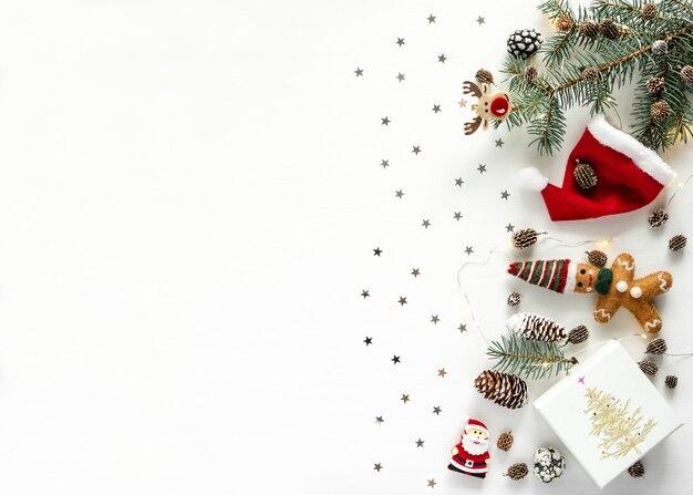 Новогодний фон. сосновые шишки, сияющие звезды, красная шляпа и фонари на белом фоне с копией пространства, плоская планировка