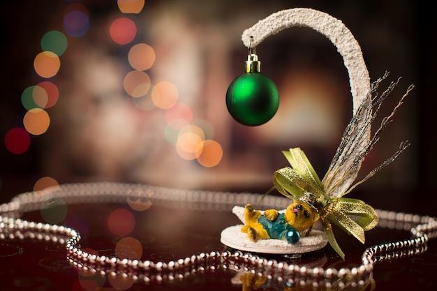 Новогодний фон с елочной игрушкой и игрушечной собачкой и боке