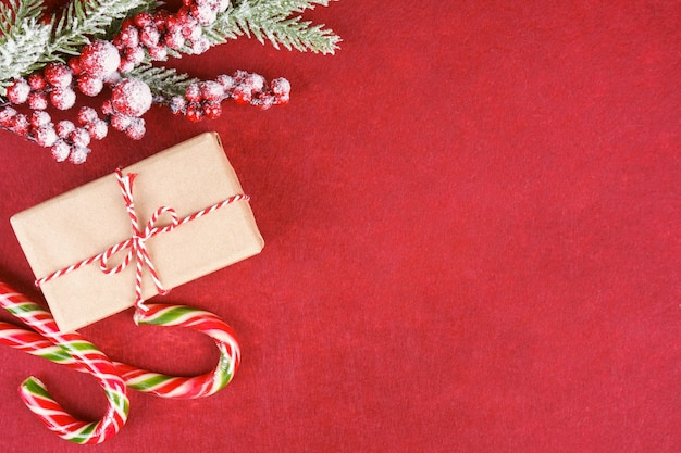 New year background with christmas tree branch, candy and gift box on red felt background with space for text. flat lay, top view.