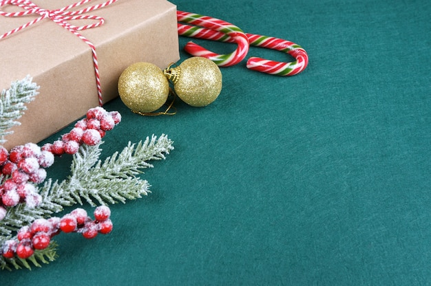 New year background with christmas tree branch, candy, golden balls and gift box on green felt background with space for text..