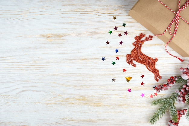 New year background with christmas tree branch, decorative deer and gift box on white wooden background with space for text. flat lay, top view.