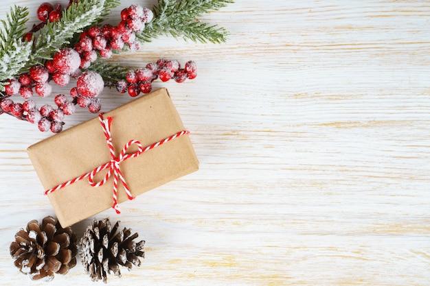 Новогодний фон с веткой рождественской елки, декоративной елью, еловыми шишками и подарочной коробкой на белом деревянном фоне с пространством для текста. плоская планировка, вид сверху.