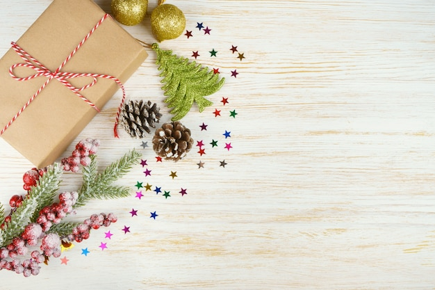 New year background with christmas tree branch, decorative fir tree, fir cones and gift box on white wooden background with space for text. flat lay, top view.