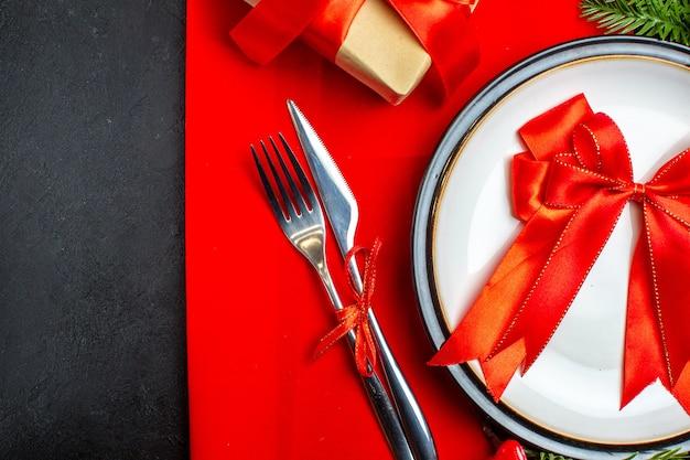 Sfondo di capodanno con nastro rosso sul piatto della cena posate set decorazione accessori rami di abete accanto a un regalo su un tovagliolo rosso