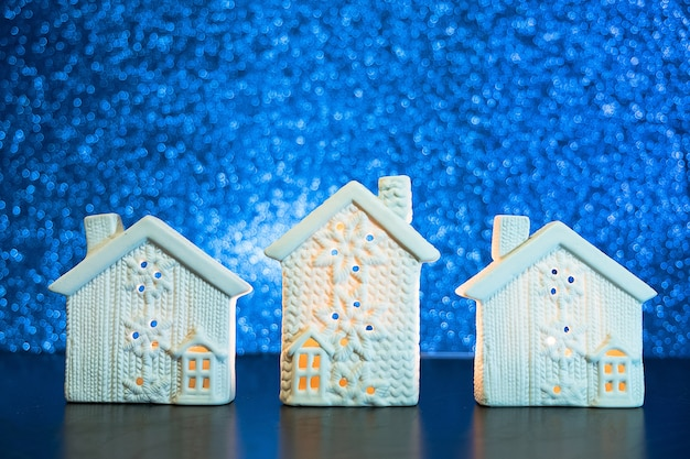 New year background with white cottages. lodges on blue blurred glitter lights background.