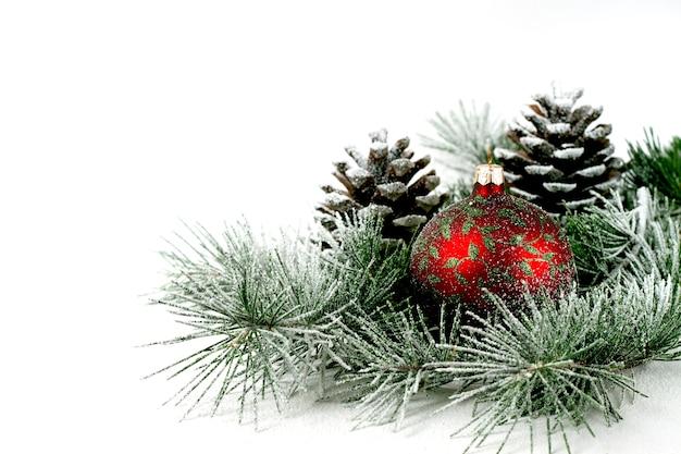 Новый год, ветка елки с шишками и красным шаром