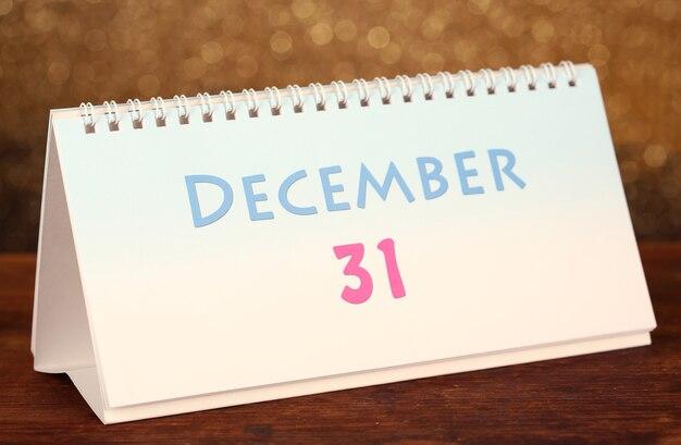 Новогодний календарь на деревянном столе, на блестящем золотом фоне