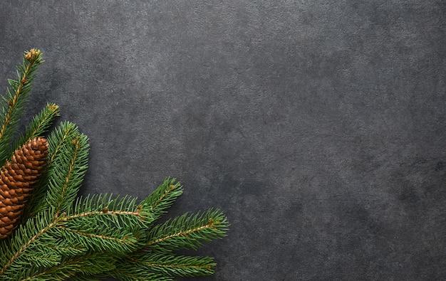 年賀状。黒のフラットレイにモミの木の枝を持つクリスマスの装飾