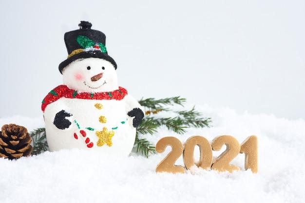 새해 카드. 크리스마스 장난감 귀여운 눈사람, 숫자 2021, 전나무 분기 눈 속에서 소나무 콘. 복사 공간.