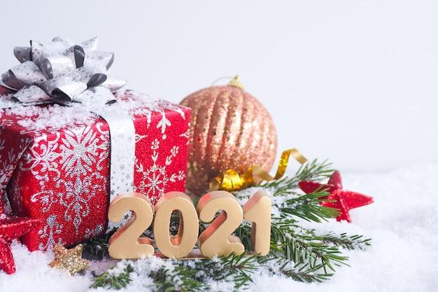 Новогодняя открытка. золотые числа 2021 года на еловых ветках со снегом, красной подарочной упаковке, звездами и елочным шаром.