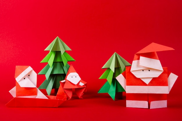 New year card handmade origami santa claus figures with trees. christmas concept winter crafted decorations studio shot on red background