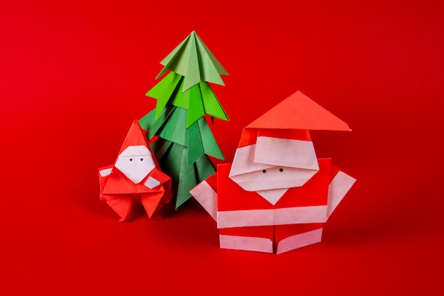 New year card handmade origami santa claus on a sleigh with trees. christmas concept winter crafted decorations studio shot close up