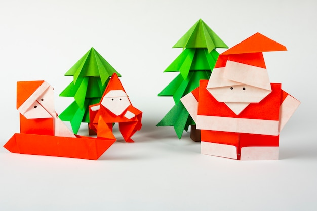 New year card handmade origami santa claus on a sleigh with trees. christmas concept winter crafted decorations studio shot isolated