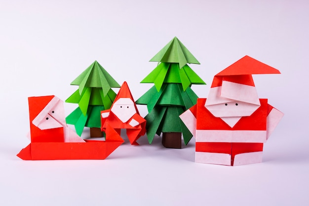 New year card handmade origami santa claus on a sleigh with trees. christmas concept winter crafted decorations studio shot on white