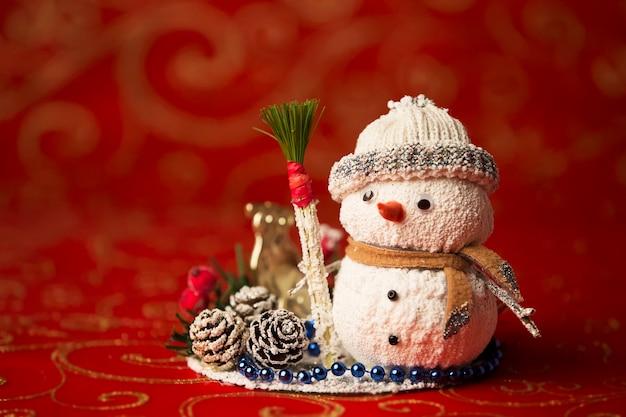 Новогодняя открытка. игрушечный снеговик. шишки засыпаны снегом. украшение на новый год