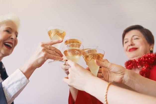 白いスパークリングワインのグラスで手を祝う新年